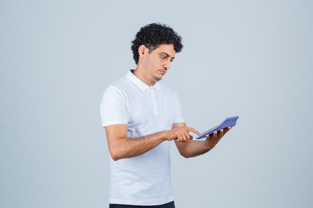 Hombre joven en camiseta blanca con calculadora y mirando pensativo, vista frontal.