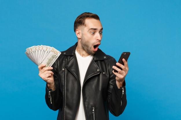 Hombre joven en camiseta blanca de chaqueta de cuero negro con ventilador de dinero en efectivo en billetes de dólar, teléfono celular aislado en retrato de estudio de fondo de pared azul. concepto de estilo de vida de personas. simulacros de espacio de copia.