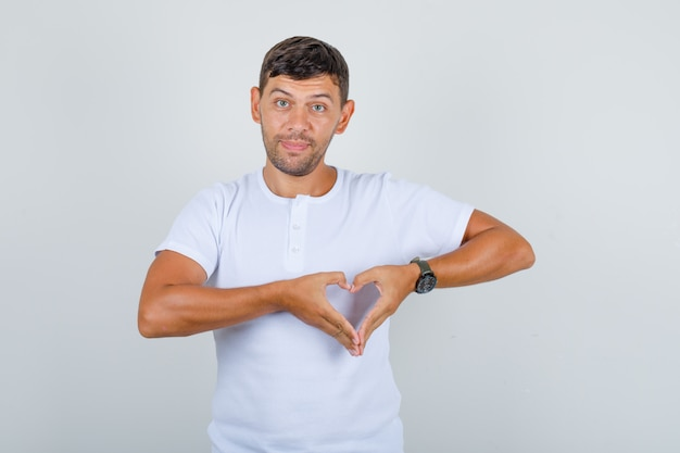 Hombre joven en camiseta blanca haciendo gesto de corazón con los dedos y mirando positivo, vista frontal.