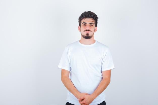 Hombre joven en camiseta blanca mirando al frente y mirando confiado