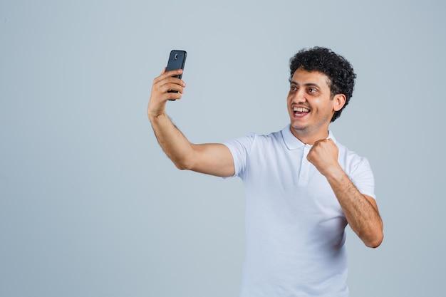 Hombre joven en camiseta blanca mirando el teléfono móvil y mirando feliz, vista frontal.