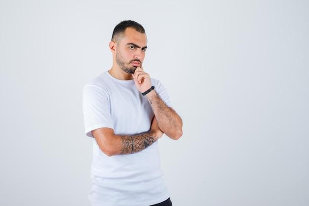 Hombre joven en camiseta blanca y pantalón negro de pie en pose de pensamiento y mirando pensativo