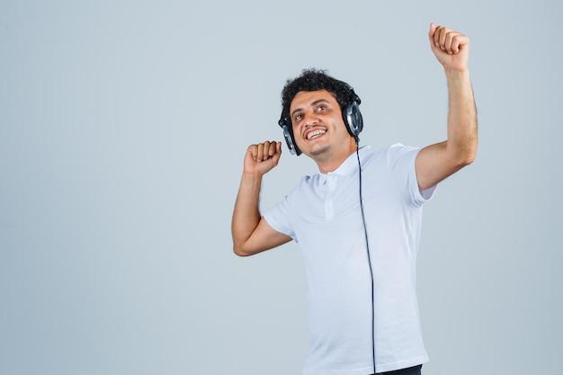 Hombre joven en camiseta blanca que muestra el gesto del ganador y mirando dichoso, vista frontal.