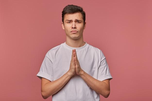 Hombre joven en camiseta en blanco, espera suerte y muestra gesto de oración, se para en rosa con expresión infeliz.