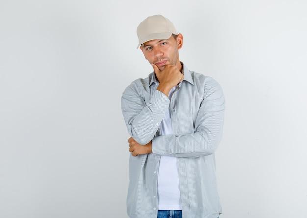 Hombre joven en camiseta con gorra, jeans de pie con la mano en la barbilla
