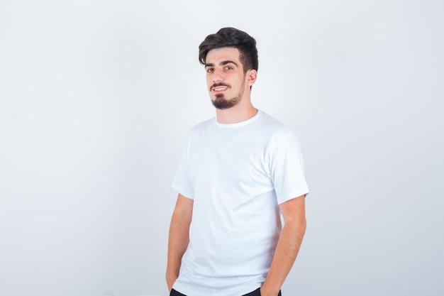 Hombre joven en camiseta mirando al frente mientras está de pie y parece feliz