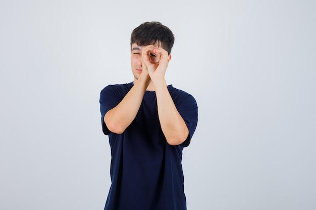 Hombre joven en camiseta negra fingiendo mirar a través del agujero con las manos y mirando curioso, vista frontal.