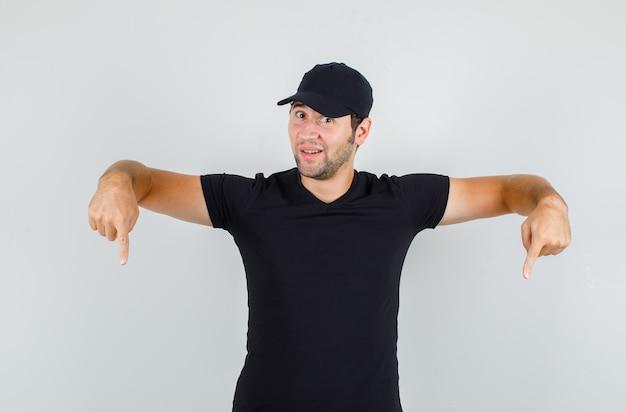 Hombre joven en camiseta negra, gorra apuntando hacia abajo con los dedos y mirando curioso