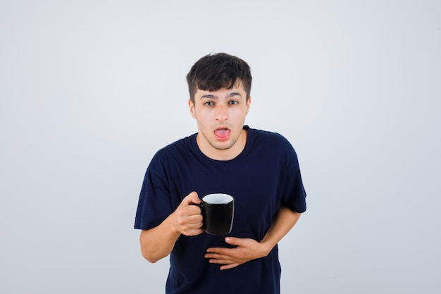 Hombre joven en camiseta negra que siente náuseas mientras sostiene una taza de té y se ve mal, vista frontal.