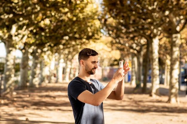 Hombre joven en camiseta de pie en la calle y hace fotos en el teléfono móvil.