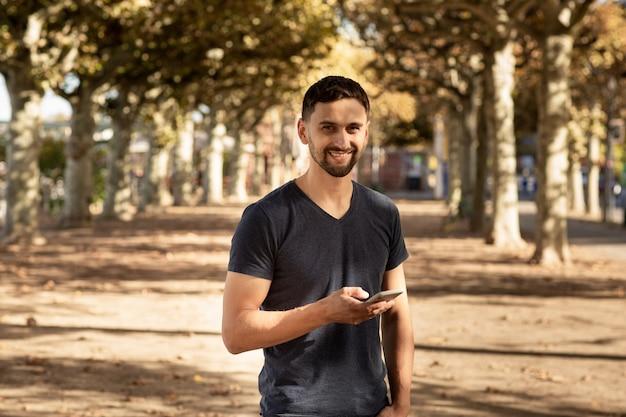 Hombre joven en camiseta de pie en la calle con teléfono móvil y escribiendo mensajes de texto.