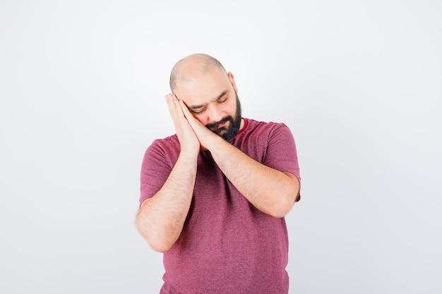 Hombre joven en camiseta rosa apoyada en la mejilla en las manos, tratando de dormir y mirando soñoliento, vista frontal.