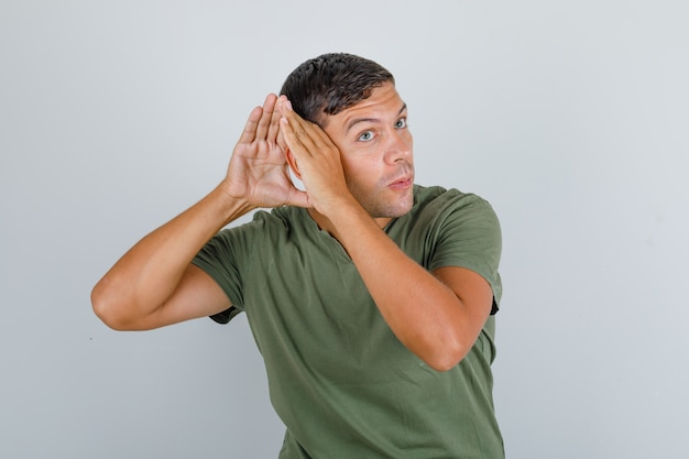 Hombre joven en camiseta verde militar escuchando algo confidencial, vista frontal.