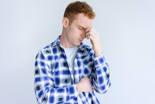 Hombre joven cansado que toca su puente de la nariz