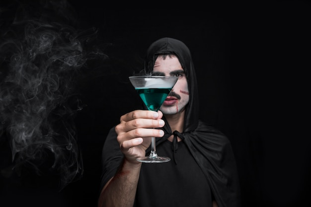 Hombre joven en la capa de halloween posando en estudio con bebidas