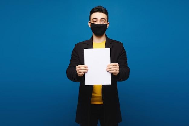 Hombre joven en una capa negra y una máscara protectora negra que presenta con una hoja de papel vacía en el fondo azul, concepto de la promoción. concepto de salud