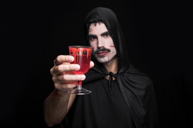 Hombre joven en capote con capucha posando en estudio con vaso de líquido rojo