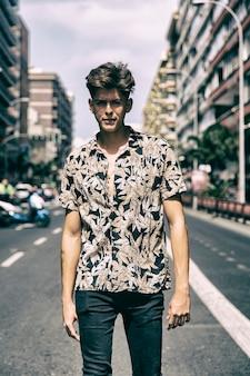 Hombre joven con cara de chico duro caminando en medio de la calle.