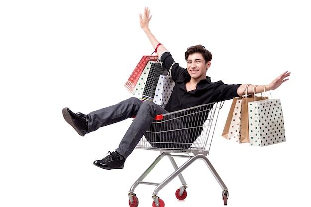 Hombre joven con el carro y los bolsos de compras aislados en blanco