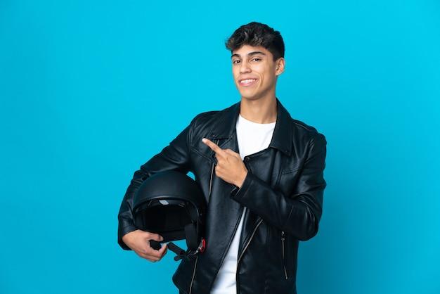 Hombre joven con un casco de moto sobre azul aislado apuntando hacia el lado para presentar un producto