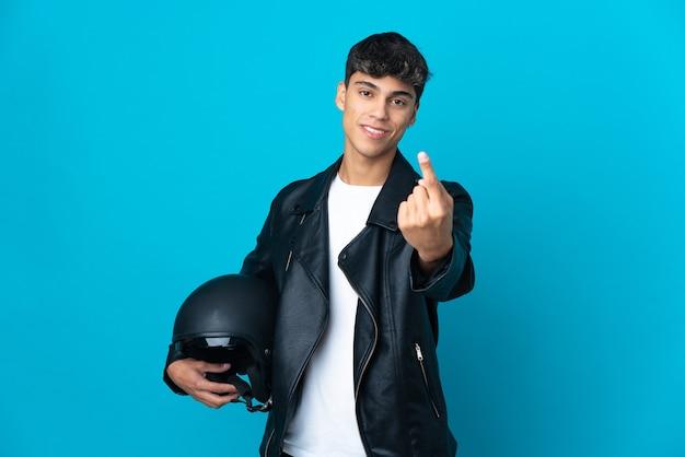 Hombre joven con un casco de motocicleta sobre azul aislado haciendo gesto que viene