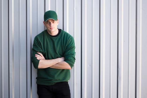 Hombre joven en casquillo con los brazos cruzados de pie contra la pared gris