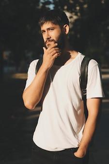 Hombre joven casual en camiseta blanca tocando oso mientras está de pie con mochila al aire libre
