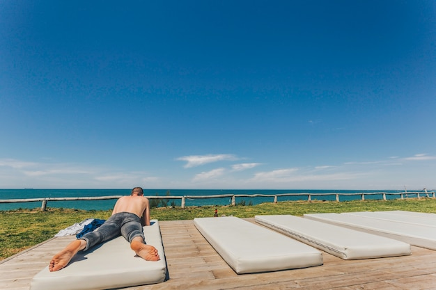 Hombre joven caucásico sin camisa y en jeans acostado en la playa sobre un colchón blanco