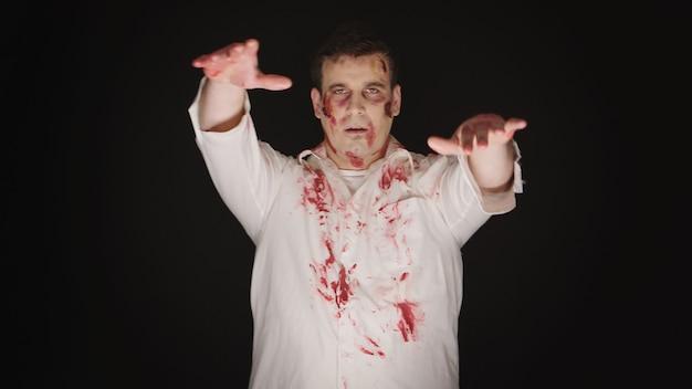 Hombre joven caucásico disfrazado de zombi para halloween.