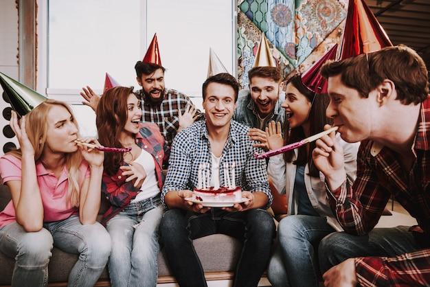 El hombre joven está celebrando cumpleaños con la compañía.