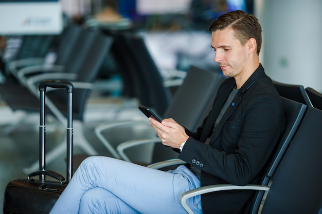 Hombre joven con celular dentro en el aeropuerto. hombre joven con smartphone en el aeropuerto mientras espera el embarque.