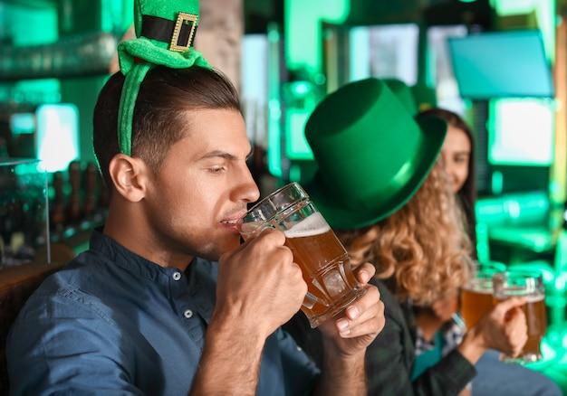 Hombre joven con cerveza celebrando el día de san patricio en pub