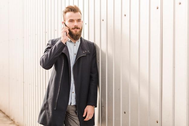 Hombre joven en chaqueta negra hablando por celular