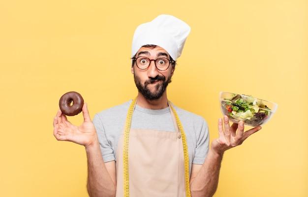 Hombre joven chef barbudo dudando o expresión incierta