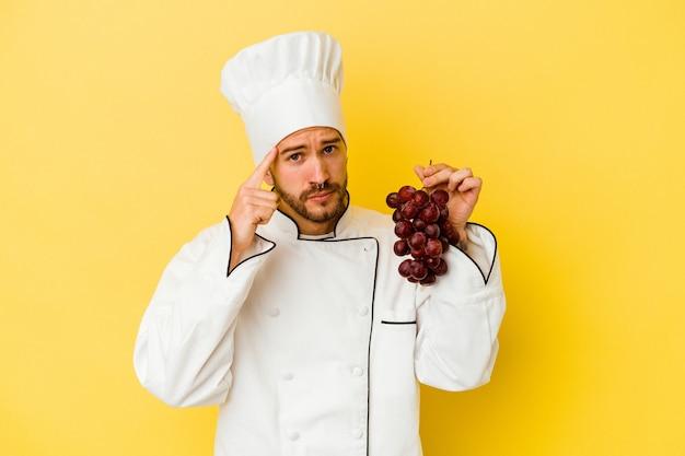 Hombre joven chef caucásico sosteniendo uvas aisladas en la pared amarilla señalando el templo con el dedo, pensando, centrado en una tarea.