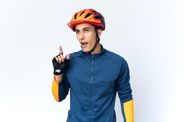 Hombre joven ciclista aislado pensando en una idea apuntando con el dedo hacia arriba