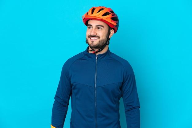 Hombre joven ciclista aislado pensando en una idea mientras mira hacia arriba