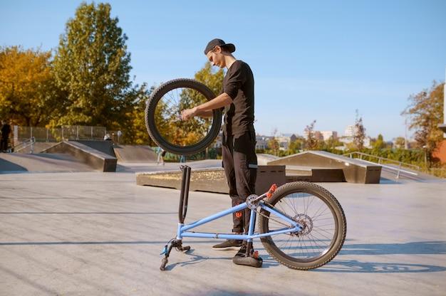 Hombre joven ciclista de bmx ajusta su bicicleta, adolescente en formación en skatepark. deporte extremo en bicicleta, ejercicio de ciclo peligroso, riesgo de montar en la calle, andar en bicicleta en el parque de verano