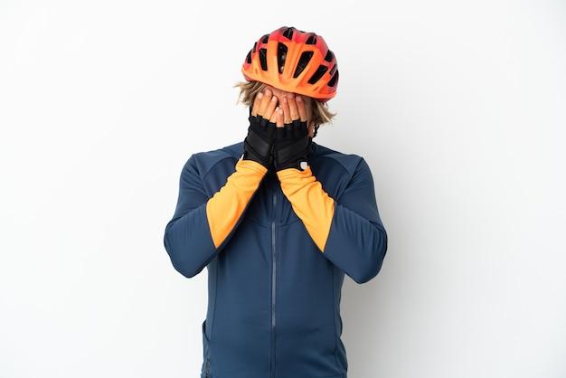 Hombre joven ciclista rubio aislado sobre fondo blanco con expresión cansada y enferma