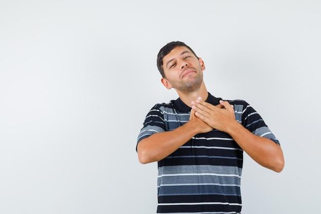 Hombre joven cogidos de la mano en el pecho en camiseta y mirando alegre, vista frontal.