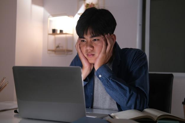 Hombre joven de collage agotado soñoliento que trabaja horas extras en el escritorio de la oficina con su computadora portátil, está a punto de quedarse dormido, la privación del sueño y el concepto de trabajo de horas extras.