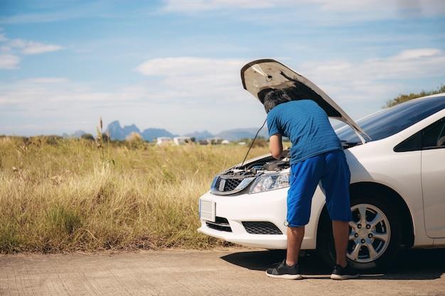 El hombre joven está comprobando los coches.