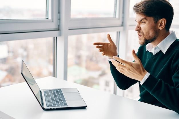 Hombre joven con una computadora portátil en un traje de negocios trabajando en la oficina y en casa en la superficie de una ventana, entrevistando en línea