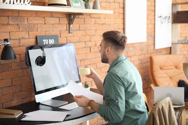 Hombre joven con computadora trabajando en casa