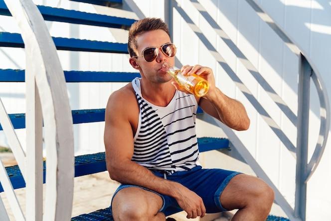 Hombre joven con estilo en gafas de sol bebiendo una cerveza fría mientras  estaba sentado en 39ee475d8608