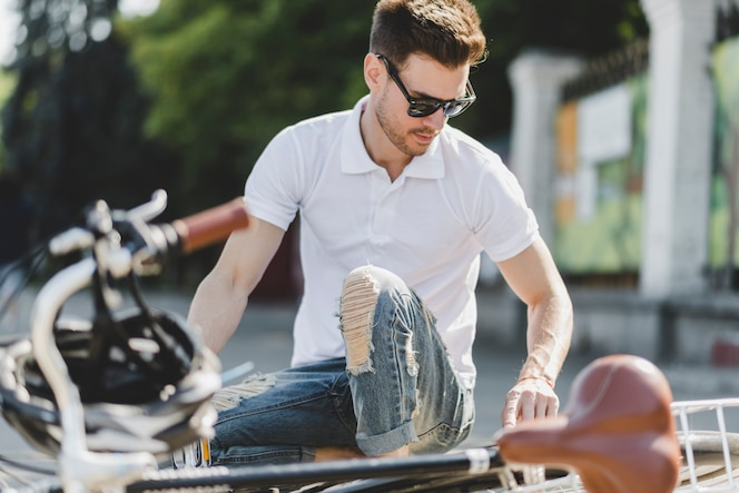 Hombre joven con estilo que repara la bicicleta en el camino