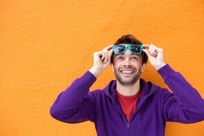 Hombre joven con expresión feliz en la cara mirando hacia arriba