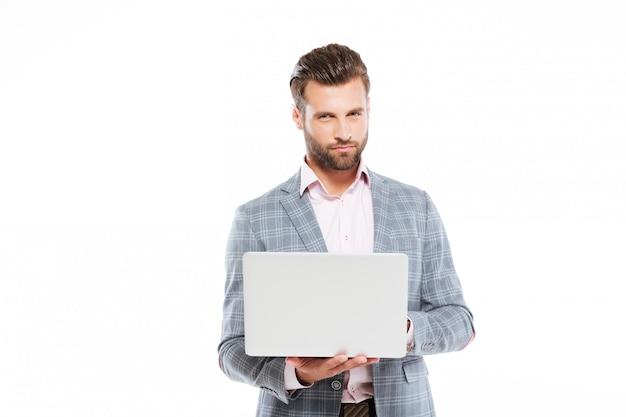 Hombre joven concentrado que usa la computadora portátil.