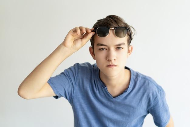 Hombre joven concentrado serio que sostiene las gafas de sol