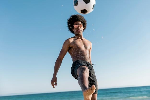 Hombre joven confiado pateando la pelota en la orilla del mar